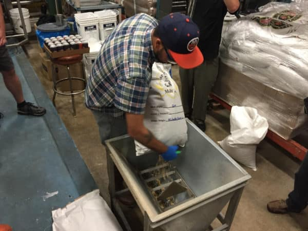 3 Floyds Brewer, Adam Conway, pouring the local corn into the hopper.