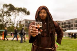 Broad Ripple Beer Fest Attendee in a Monk Costume holding out the collectible festival glass